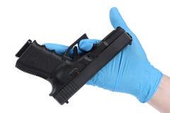 Hand im Handschuh hält Pistole Stockfoto