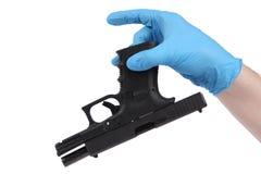 Hand im Handschuh hält Pistole Lizenzfreie Stockfotografie
