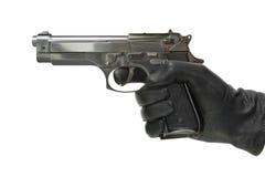 Hand im Handschuh mit Pistole Lizenzfreie Stockbilder