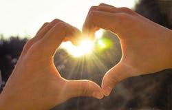 Hand im Herzen vom Liebessonnenschein Stockfotografie