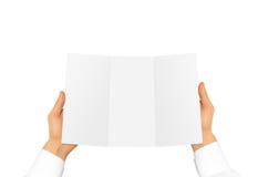 Hand im weißen Hemdsärmel, der leeres Offsetpapier im Han hält Stockfotos