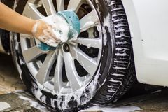 Hand image is holding sponge and car wash.Wheel area. royalty free stock photos