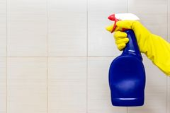 Free Hand In Yellow Rubber Glove Holding A Blue Cleaning Spray Bottle Close Up With Copy Space. Washing, Cleaning And Wiping Concept Stock Image - 135183941