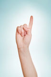 Hand with index finger raised up. Caucasian white female hand with index finger raised up and pointing stock photo