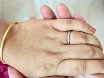Hand in hand of an Indian couple in love. A platinum ring in the ring finger of an Indian women having her hand in the hand of her husband Stock Photos