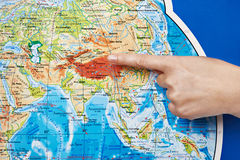 Hand indicates location on world map. Royalty Free Stock Images