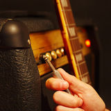Hand with input jack near combo amplifier for guitar on the black background. Royalty Free Stock Photography