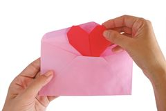 Hand inputting red heart paper origami into pink envelope. Isolated on white background for Valentine`s day concept Royalty Free Stock Photos