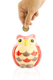 Hand insert coin into an owl piggy bank Royalty Free Stock Photo