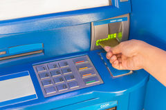 Hand insert credit card to ATM bank cash machine for withdraw mo Royalty Free Stock Images