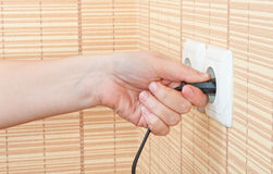 Hand insert the plug into the power Stock Photos
