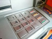 Hand inserting ATM card into bank machine to withdraw money. Hand inserting ATM card into bank to withdraw money Stock Images