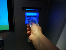 Hand inserting ATM card into bank machine to withdraw money.  Royalty Free Stock Image