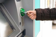 Hand inserting ATM card into bank machine to withdraw money.  Royalty Free Stock Images