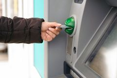 Hand inserting ATM card into bank machine to withdraw money.  Stock Photography