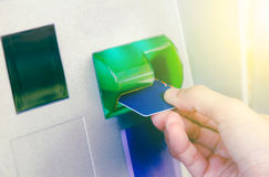 Hand inserting ATM card into bank machine to withdraw money,Hand Royalty Free Stock Photos