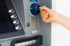 ATM and credit card. Hand inserting ATM credit card royalty free stock photo
