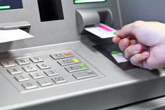 Hand inserting ATM credit card into bank machine to withdraw mon Stock Photo