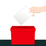 Hand Inserting Ballot Vote. Hand inserting a paper ballot voting on a red ballot box Royalty Free Stock Photos