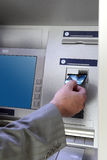 Hand inserting card into cash dispense Stock Photo