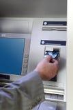 Hand inserting card into cash dispense. Man's hand inserting card into cash dispense Stock Photo