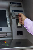 Hand inserting card into cash machine Stock Photos