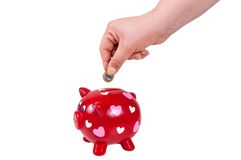 Hand inserting coin into piggy bank Royalty Free Stock Photo