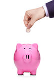 Hand inserting coin into piggybank royalty free stock image