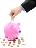 Hand inserting a coin into a pink piggy bank Stock Image