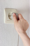Hand inserting electric plug in the socket on the wall Stock Photos