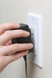 Hand inserting an electrical plug into a wall socket Stock Photo