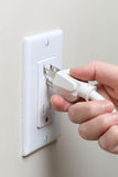 Hand inserting an electrical plug into a wall socket Stock Image