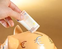 Hand inserting a fifty euro banknote into a piggy bank, concept for business and save money. Detail of a hand inserting a fifty euro banknote into a piggy bank Royalty Free Stock Image