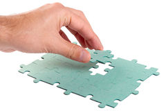 Hand inserting green jigsaw puzzle Royalty Free Stock Photography