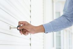 Hand inserting key in keyhole Stock Photos