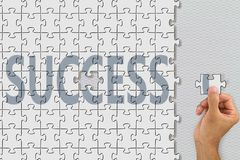 Hand inserting last missing piece jigsaw of word success stock photo