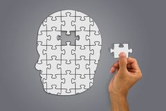 Hand inserting missing brain jigsaw in white man`s head shape. Business concept royalty free stock photo