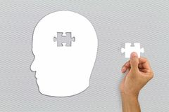Hand inserting missing brain jigsaw in white man`s head shape. Business concept royalty free stock images