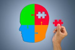Hand inserting missing jigsaw in man`s head shape stock images