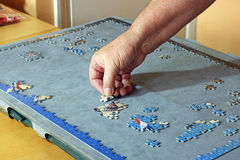 Hand inserting a piece of jigsaw puzzle. Royalty Free Stock Images