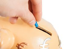 Hand inserting a pill into a piggy bank, concept for save money. Hand inserting a pill into a piggy bank on white background with space for text, concept for Royalty Free Stock Photography
