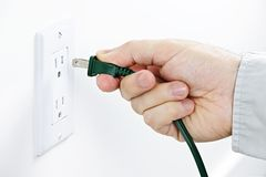 Hand inserting plug into outlet Royalty Free Stock Images