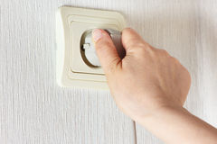 Hand inserting a plug in the socket on the wall Royalty Free Stock Photo