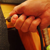 Hand inserts input jack to combo amplifier for guitar. Royalty Free Stock Photo