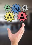 Hand interacting with people in cogs graphics against office background Royalty Free Stock Photos