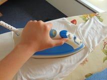 Hand ironing white t-shirt. Hand ironing a white t-shirt on an ironing board Stock Photo