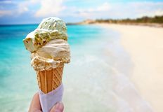 Free Hand Is Holding The Vanilla Ice Cream. In The Background Is Blue Sky, Sea Nd Sandy Beach. This Is Situated In Tropical Resort Stock Photos - 151633423