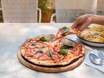Hand ist, herausziehend halten und eine Scheibe von Pizza margherita den Behälter lizenzfreie stockbilder
