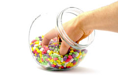 Hand in a jar with colored candies isolated Stock Photos