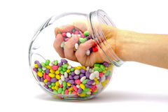 Hand in a jar with colored candies isolated. Hand in a jar with colored candies on a white background Stock Image